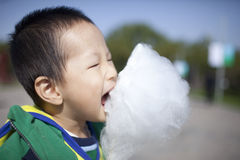 Asian boy eating cotton candy happily Stock Photos