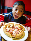 Asian boy eating pizza. Asian Boy ready to eat a pizza with Happy and Enjoy Stock Photos