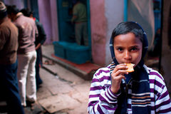 Asian boy eats cookies on a cold evening in the st. VARANASI, INDIA: Unidentified boy eats cookies on a cold evening in the street. Varanasi has a population 1,5 Stock Photography