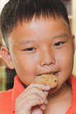 Asian boy eats a piece of biscuit Royalty Free Stock Images