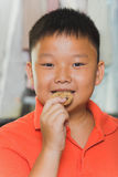 Asian boy eats a piece of cookie Stock Photography