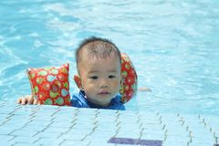 Asian boy at edge of baby pool Royalty Free Stock Images