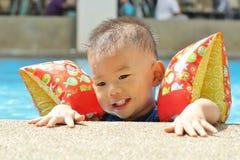 Asian boy at edge of baby pool Royalty Free Stock Photos