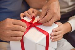 Asian boy and elderly man holding on red ribbon of white gift bo Stock Photos