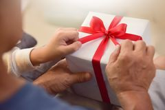 Asian boy and elderly man holding on red ribbon of white gift bo Royalty Free Stock Photography