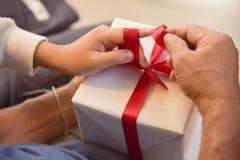 Asian boy and elderly man holding on red ribbon of white gift bo Stock Photo
