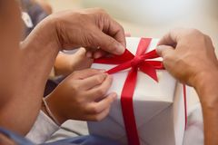 Asian boy and elderly man holding on red ribbon of white gift bo Stock Photography