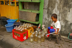 Asian boy with empty petrol bottles Stock Photo