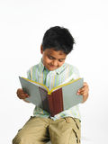 Asian boy engrossed in a book royalty free stock images