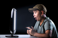 Asian boy excited with computer game. With expressing face Royalty Free Stock Photography