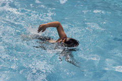 Asian boy front crawl swims in swimming pool Stock Photos