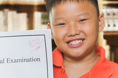 Asian boy with full score examination sheets Stock Images