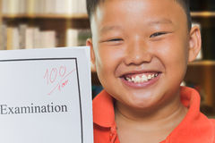 Asian boy with full score examination sheets Royalty Free Stock Photography