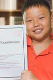 Asian boy with full score examination sheets Royalty Free Stock Photo