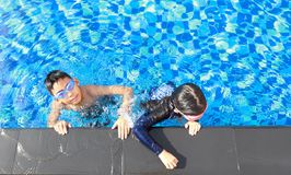Asian boy and girl swimming. Asian boy and girl happy swimming in a pool Stock Photos