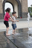 Asian boy and girl play by fountain Royalty Free Stock Photo