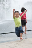 Asian boy and girl play by fountain Stock Photography