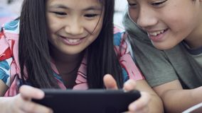 Asian boy and girl playing game on mobile phone together with smiling faces. Child playing with tablet or smartphone at home , Asian boy and girl playing game stock video