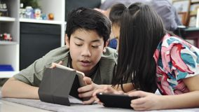 Asian boy and girl playing game on mobile phone together with smiling faces. Child playing with tablet or smartphone at home , Asian boy and girl playing game stock footage