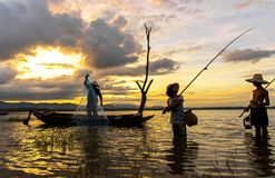 Asian boy and girl playing in the river with fisherman,. In the morning sunrise, Thailand Stock Photos