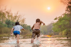Asian boy and girl playing in the river. At sunrise Royalty Free Stock Image