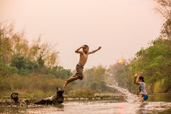 Asian boy and girl playing in the river. With sunset Stock Photo