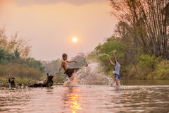 Asian boy and girl playing in the river. With sunset Royalty Free Stock Image