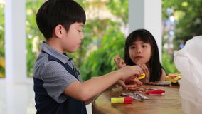 Asian boy and girl playing with slice of bread at home stock video footage