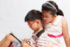 Asian boy and girl playing tablet Stock Image