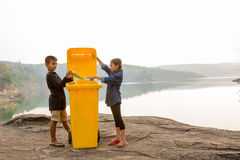 Asian boy and girl throwing trash into litter bin Royalty Free Stock Image