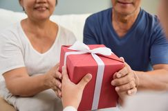 Asian boy giving a red gift box to grandfather and grandmother. Close up on hands. Asian Boy giving a red gift box to his grandfather and grandmother for royalty free stock image