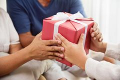 Asian boy giving a red gift box to Grandfather and Grandmother. Close up on hands. Asian Boy giving a red gift box to his Grandfather and Grandmother for royalty free stock photo