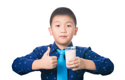 Asian boy giving you thumbs up with glass of milk in hand, isola Stock Photo
