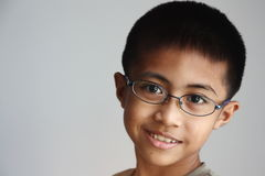 Asian Boy with Glasses. A smiling intelligent looking Asian boy head shot or close up wearing glasses Stock Images