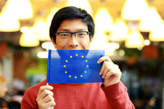 Asian boy in glasses holding flag of europe union Royalty Free Stock Photos