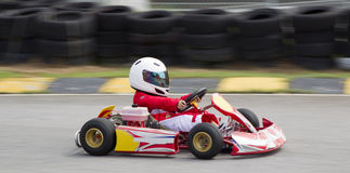 Asian boy in a go kart. Young asian boy in race suit and helmet racing in a go kart Stock Images