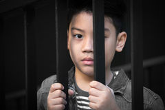 Asian boy Hand in jail looking out the window Stock Images