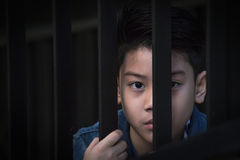 Asian boy Hand in jail looking out the window Stock Photos