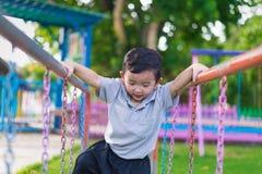 Asian boy hang the metal bar at outdoor playground. Asian boy hang the metal bar for balance at outdoor playground Royalty Free Stock Photography
