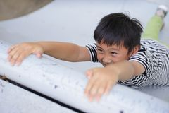Asian boy hanging on wall on hands and trying to climb up.  stock photos