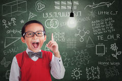 Asian boy has idea under lit bulb in classroom royalty free stock photos