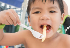 Asian boy is having fries snack Royalty Free Stock Photos