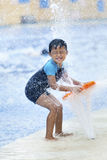 Asian boy having fun at a waterpark. Summer fun at the waterpark. Boy playing with a fountain Stock Image