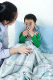 Asian boy having respiratory illness helped by health profession Stock Images