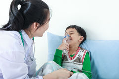 Asian boy having respiratory illness helped by health profession Stock Photos