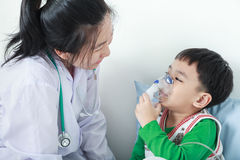 Asian boy having respiratory illness helped by health profession Stock Image