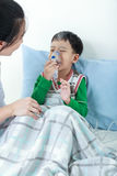 Asian boy having respiratory illness helped by health profession Royalty Free Stock Images