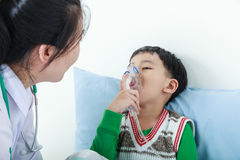 Asian boy having respiratory illness helped by health profession Royalty Free Stock Photos