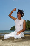 Asian boy with headset on beach. Asian boy with headset on tropical pristine beach listening to music and enjoying royalty free stock image