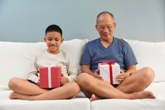 Asian Boy and his Grandfather holding gift boxes. Stock Photography